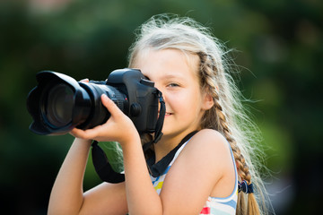 friendly female child taking pictures with camera in park