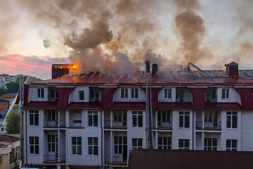 Burning fire flame with smoke on the apartment house roof in the city, firefighter on the ladder extinguishes fire