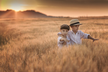 The hugged children stand in the field of wheat