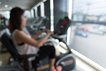 blurred woman cycling burn fat on bicycle cardio machine in fitness gym