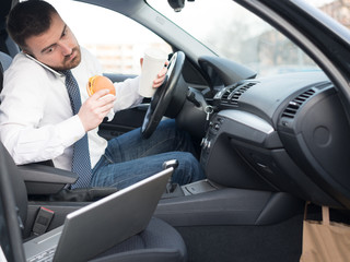 Man eating an hamburger and working seated in car
