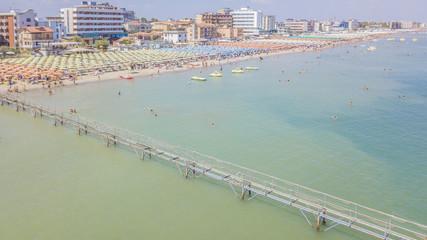 Dalla riviera romagnola vista aerea di ombrelloni colorati disposti in fila sulla spiaggia di Riccione. le persone in spiaggia prendono il sole o si riparano all' ombra prima di un bagno a mare.