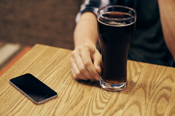 A glass of beer on the table next to the phone in the bar