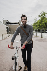 portrait of smiling young man with headphones pushing his bike