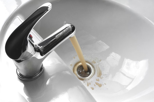 Water Tap With Running Dirty Muddy Water in a Sink