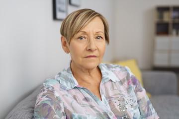 ältere frau mit kurzen haaren sitzt auf dem sofa