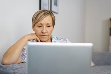ältere frau schaut konzentriert auf ihren laptop