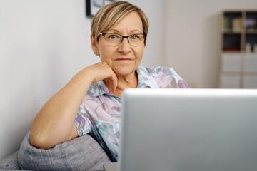 lächelnde ältere frau mit ihrem notebook zu hause