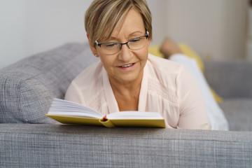 ältere frau liegt auf dem sofa und liest ein buch