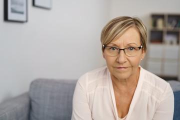 moderne frau mit brille in ihrem wohnzimmer