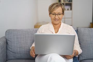moderne ältere frau sitzt auf dem sofa und surft im internet