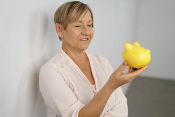 ältere frau mit kurzen haaren schaut lächelnd auf ein gelbes sparschwein