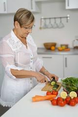 ältere frau bereitet einen frischen salat zu
