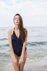 Woman with long dark hair in a piece-blue bathing suit on the beach. Summer photo concept