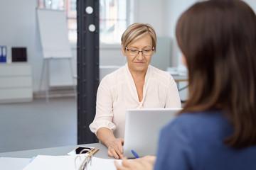 ältere geschäftsfrau arbeitet im büro am notebook