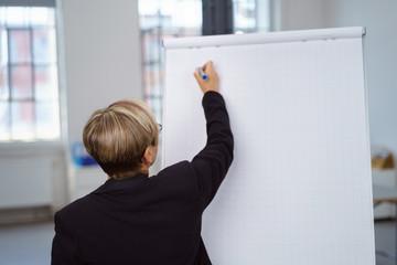 ältere geschäftsfrau schreibt etwas an ein flipchart