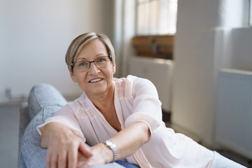 moderne ältere frau entspannt auf dem sofa