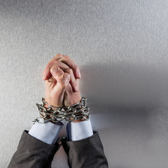 joined businessman hands tied with chain praying for corporate crime