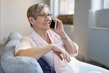 entspannte ältere frau telefoniert zu hause