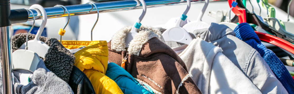 used baby winter clothes, jackets and coats displayed on rack