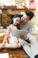 Father using digital tablet with daughter