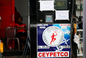 A worker rests at a closed Ceylon Petroleum fuel station near the highway entrance in Galle