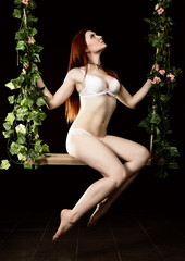 redhead woman in underwear on a swing with creepers on a dark background
