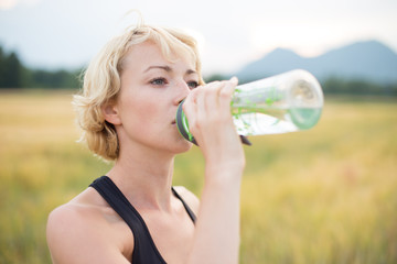 Fitness woman drinking water while workin out in nature.