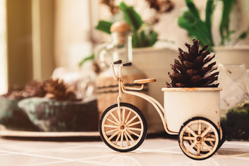 Soft Focus Picture of Still Life Vintage Metal Bicycle Vase with Pine Cone Decorate on Table