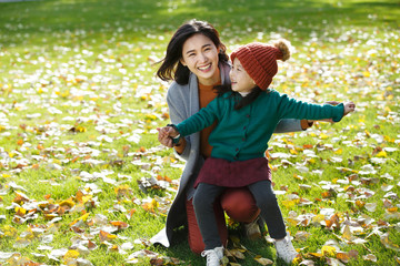 Portrait of mother and daughter playing in park in autumn