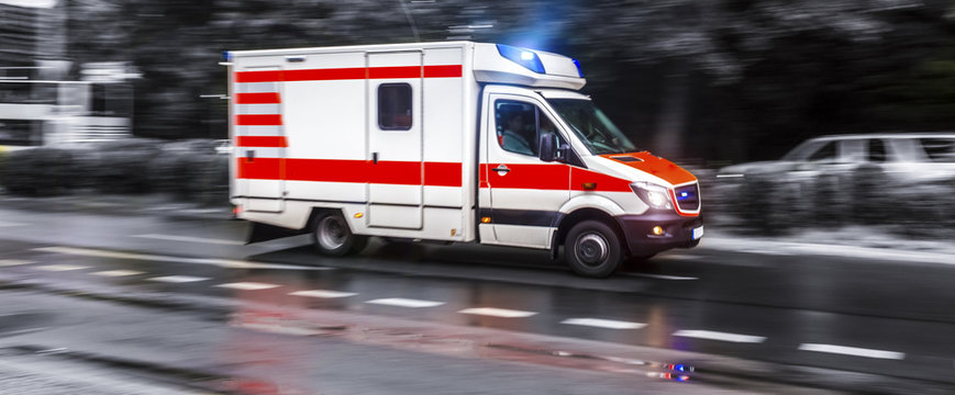 colored ambulance car speeding in black and white