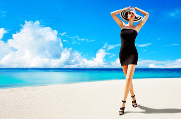 Summer fashion image. Beautiful woman with black dress, heels shoes, and a hat walking on the sunny beach.