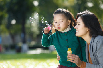 Daughter with mother blowing bubbles