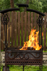 Burning wood bonfire in brazier outdoor. Preparation for cooking barbecue outside. Selective focus