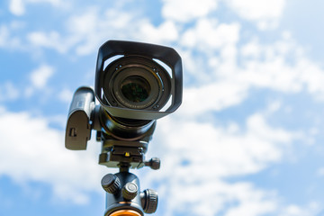 Digital camera closeup on a background of sky and clouds. Shooting on location and nature.