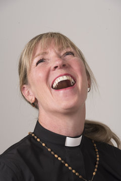 Portrai of a woman priest with blond hair and laughing