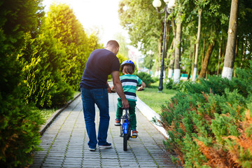 Dad teaches his son riding on bicycle in summer park. Back view