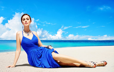Summer fashion image. Woman with blue elegant dress,gold heels shoes,earrings,bracelet, and necklace laying on the beach.