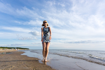 Happy young woman in short dress jumping on the beach