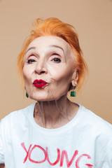 Mature redhead fashion woman blowing kisses.