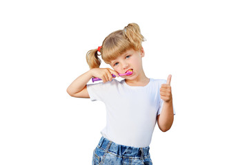 A little girl is brushing her teeth. She likes to do this, so she has healthy and beautiful teeth.