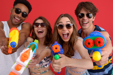 Young happy group of friends with water toy guns