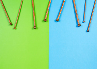 Wooden bamboo knitting needles arranged as frame border on colorful background
