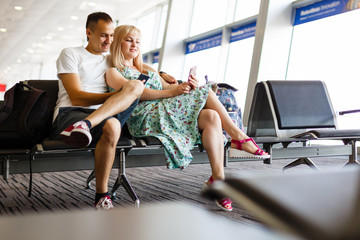 Young Couple sitting with phone and book at the waiting hall in the airport