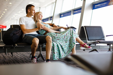 Young couple resting on the chairs at the waiting room of the airport. Long waiting for the airplane