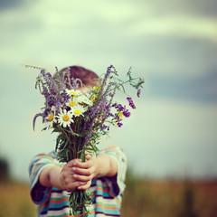 Little kid boy holding bouquet of fields flowers. Child giving flowers.