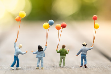 Family and kid concept. Group of children miniature figure with colorful balloons standing, walking...