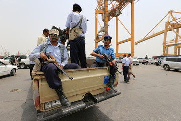 Police troopers ride on the back of a patrol truck during a visit by a U.N. delegation to the Red Sea port of Hodeidah, Yemen