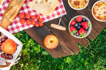 Zelfklevend Fotobehang Picknick Picnic food on wooden board and green grass with copyspace