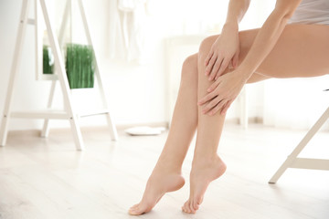 Woman touching smooth skin on leg at home. Epilation concept